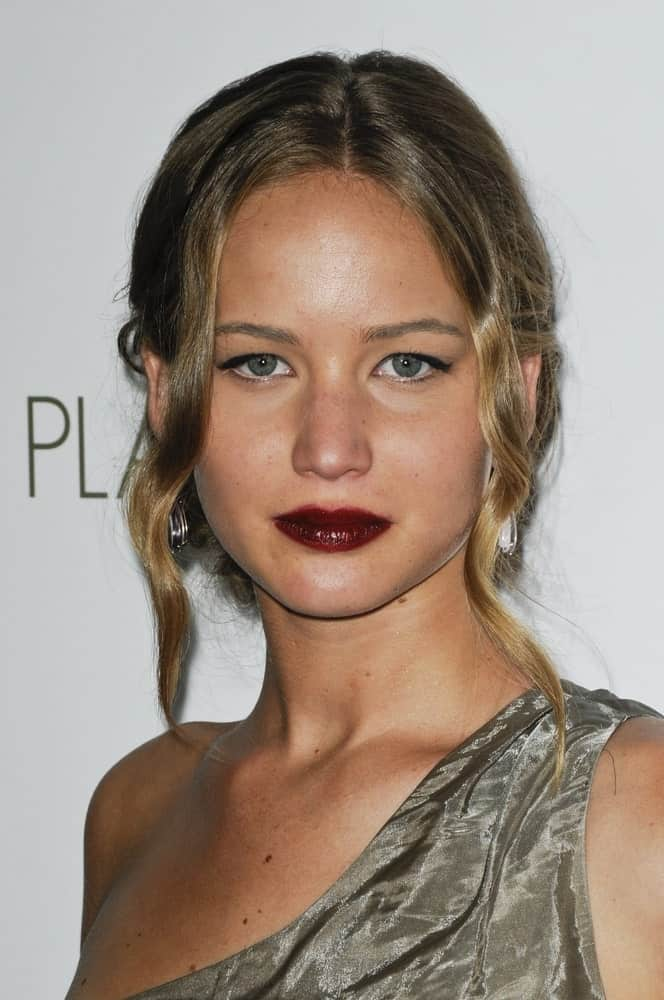 Jennifer Lawrence went with dark red lips to match with her messy bun hairstyle incorporated with loose wavy tendrils at