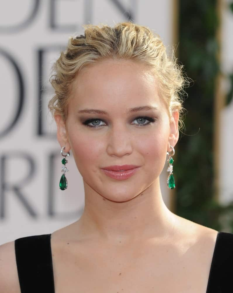Jennifer Lawrence flaunted her beautiful earrings with a messy and highlighted bun hairstyle with loose tendrils when she arrived at the 68th Annual Golden Globe Awards on January 16, 2011 in Beverly Hills, CA.