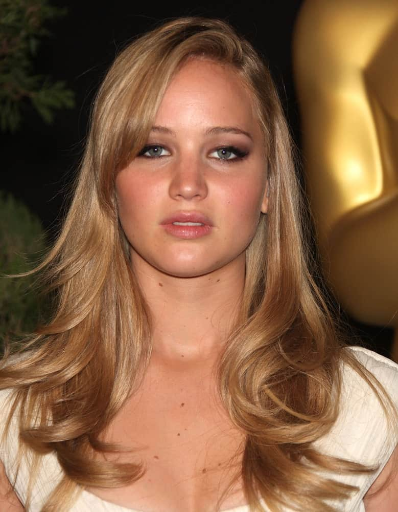 Jennifer Lawrence paired her simple white outfit with a long blond hair incorporated with wavy layers and long side-swept bangs at the 83rd Academy Awards Nominees Luncheon on Feb 7, 2011 in Beverly Hills, CA.