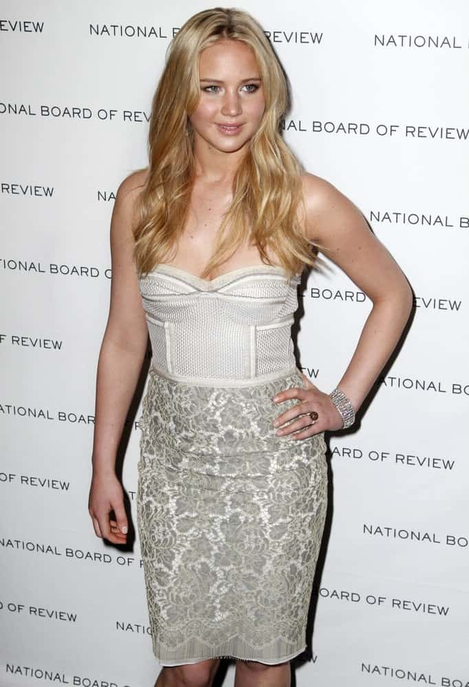 Actress Jennifer Lawrence attended the 2011 National Board of Review of Motion Pictures Gala at Cipriani's on January 11, 2011 in New York City. She came wearing a gray short dress with floral details and a center-parted long sandy blond hairstyle with a slight tousle.
