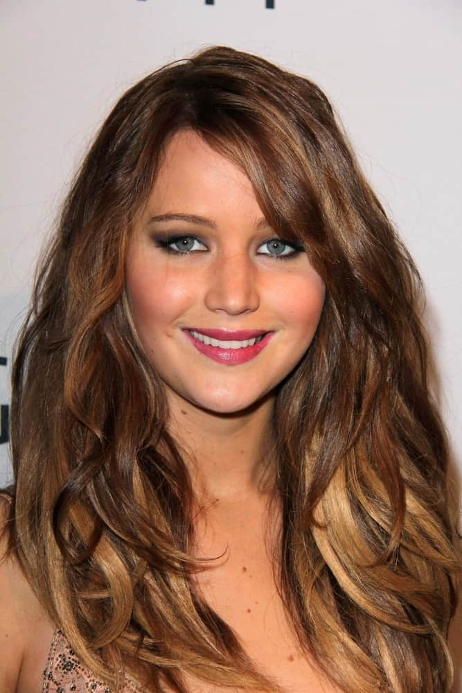Jennifer Lawrence had a long, loose, tousled and layered hairstyle with side-swept bangs at the Hollywood Reporter Celebrates the 85th Academy Awards Nominees event at the Spago on February 4, 2013 in Beverly Hills, CA.