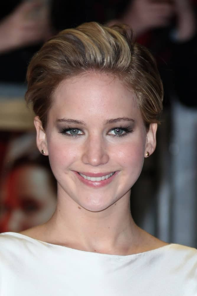 Jennifer Lawrence attended 'The Hunger Games : Catching Fire world premiere' held at Odeon Leceister Square in London on November 11, 2013. She paired her simple white outfit with a lovely side-swept highlighted pixie hairstyle.