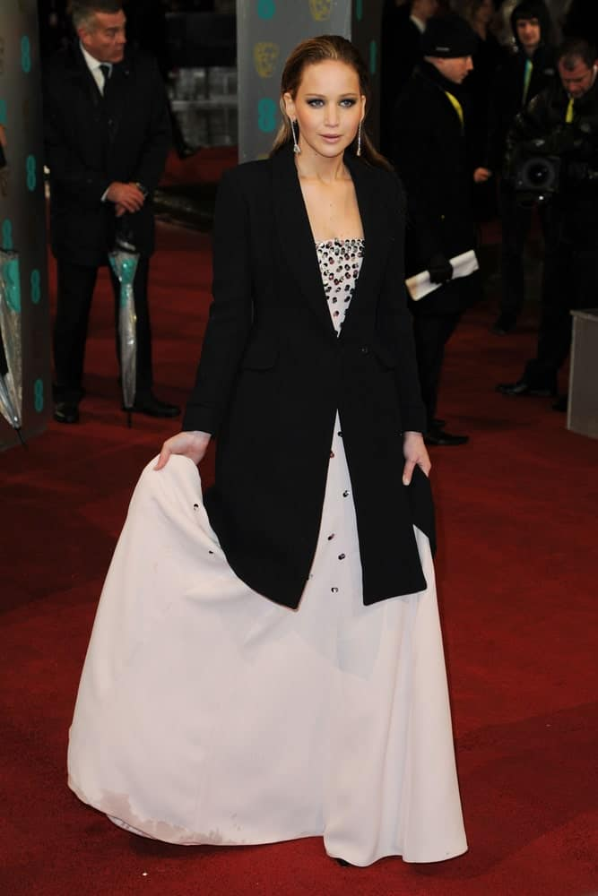 Jennifer Lawrence attended the EE BAFTA Film Awards 2013 at the Royal Opera House, Covent Garden, London. She came wearing a black coat over her white dress to pair with her slicked back loose long hair that has a dark brown tone.