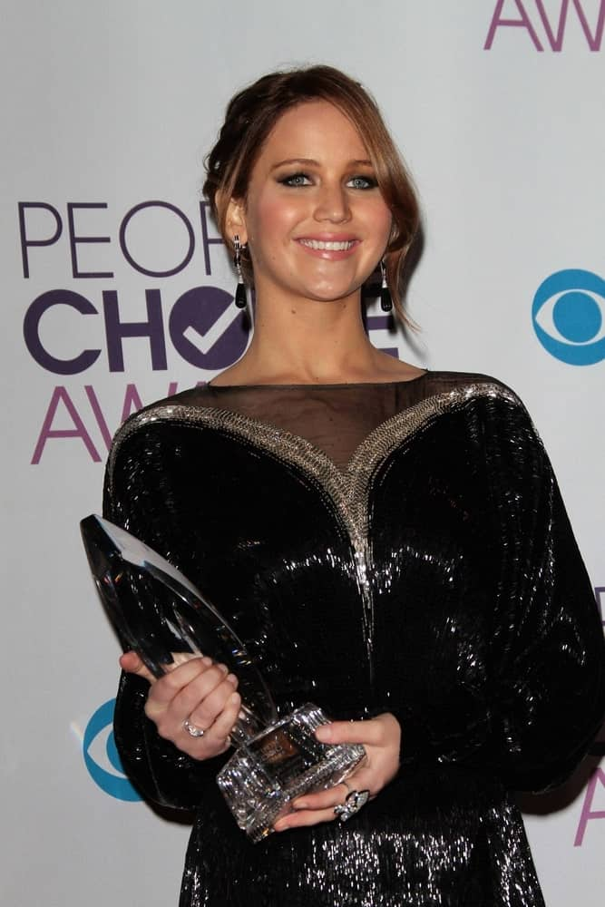 Jennifer Lawrence's shiny black dress paired quite well with her dark brown upstyle hair with loose and long side-swept bangs at the 2013 People's Choice Awards Press Room, Nokia Theatre on January 9, 2013 in Los Angeles, CA.