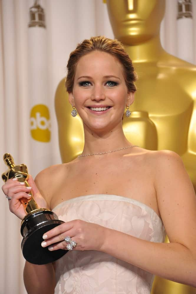 Jennifer Lawrence paired her elegant white dress with a bright smile and slicked back bun hairstyle at the 85th Academy Awards at the Dolby Theatre, Los Angeles on February 24, 2013 Los Angeles, CA.