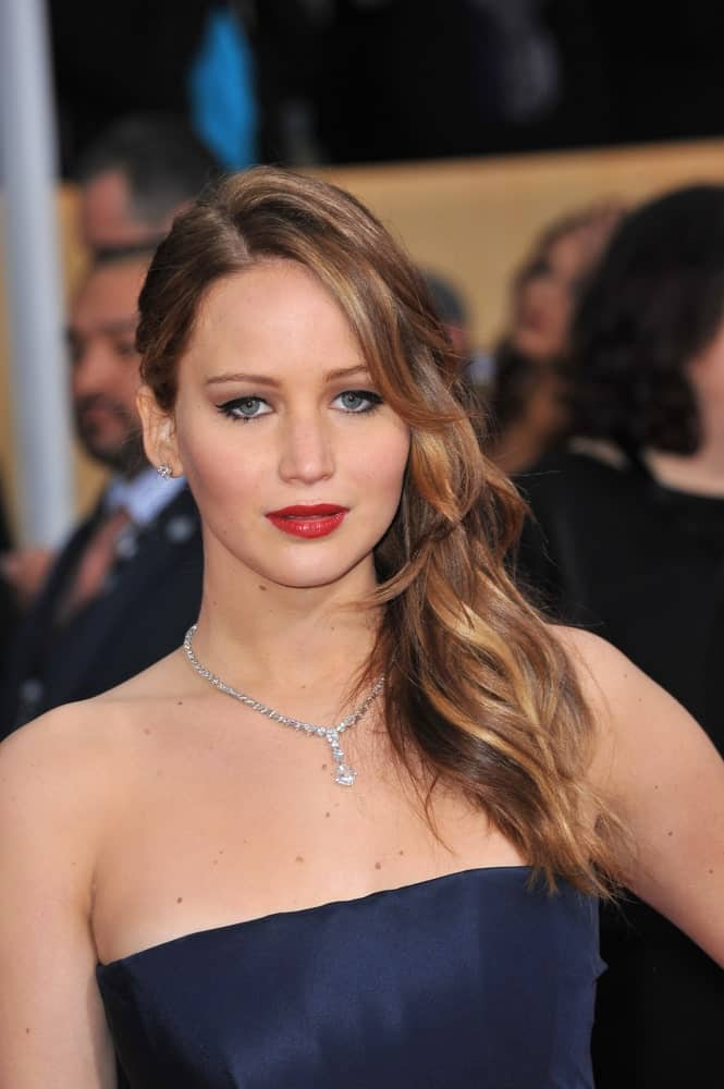 On January 27, 2013, Jennifer Lawrence paired a navy blue strapless dress to her elegant loose side-swept layered long hairstyle with highlights and long side-swept bangs at the 19th Annual Screen Actors Guild Awards at the Shrine Auditorium, Los Angeles.