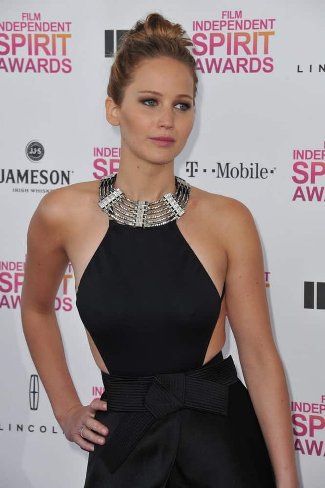 Jennifer Lawrence's lovely smokey eyes and sexy black dress was complemented by her simple yet elegant high bun hairstyle with highlights at the 2013 Film Independent Spirit Awards on the beach in Santa Monica. February 23, 2013 Santa Monica, CA.