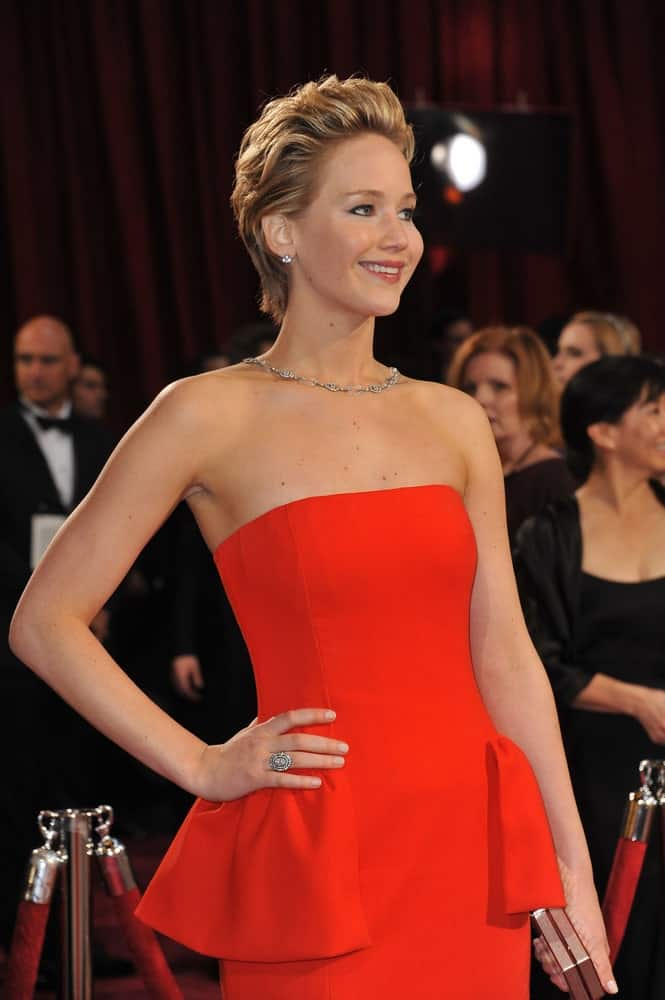 On March 2, 2014, Jennifer Lawrence was at the 86th Annual Academy Awards at the Hollywood & Highland Theatre, Hollywood. She wore a simple yet stunning red dress that she paired with a slicked-back short hairstyle with a slight pompadour look.