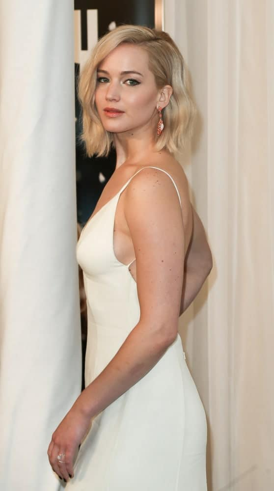 Actress Jennifer Lawrence paired her elegant white long dress with a wavy bob that has a tousled and side-swept finish at the