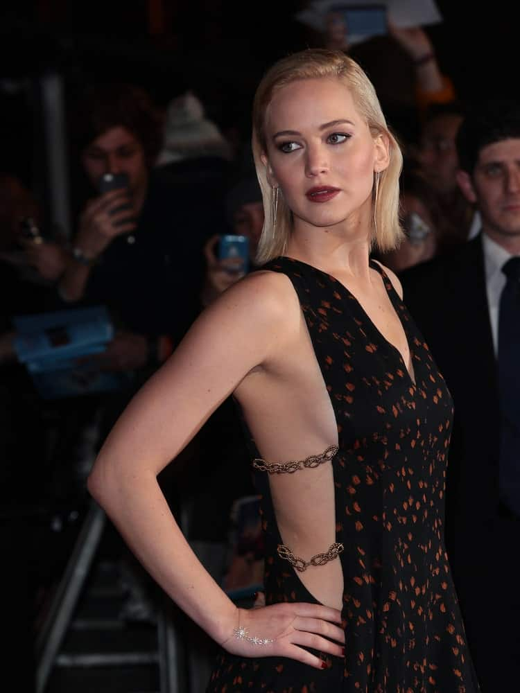 Jennifer Lawrence paired her sexy and lovely black dress with a slicked back and side-parted blond hairstyle at The Hunger Games: Mockingjay - Part 2 - UK film premiere on Nov 5, 2015 in London.