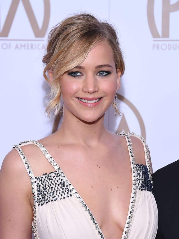 Jennifer Lawrence flashed her lovely smile when she arrived at the 26th Annual Producers Guild Awards on January 24, 2015 in Century City, CA. She wore a sexy white dress that paired well with her messy upstyle incorporated with wavy side-swept bangs.