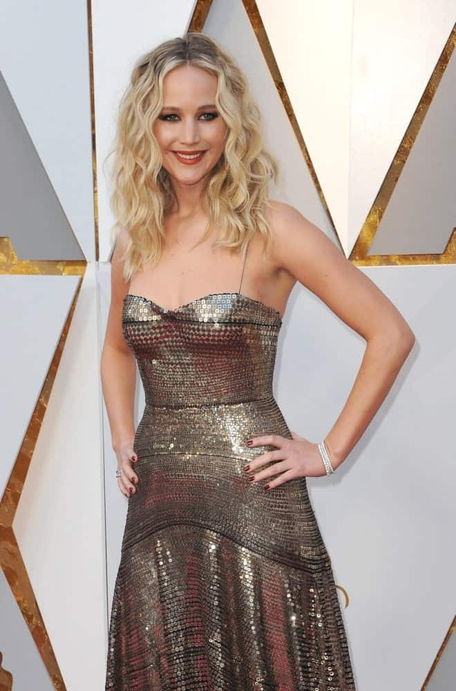 Jennifer Lawrence paired her fashionable sequined dress with a wavy and tousled blond hairstyle with highlights resting on her shoulders at the 90th Annual Academy Awards held at the Dolby Theatre in Hollywood on March 4, 2018.