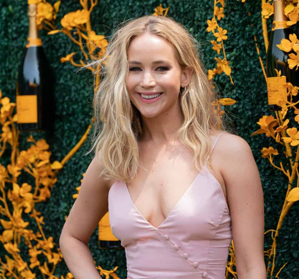 On June 1, 2019, Jennifer Lawrence wore a dress by Rosie Assoulin at the 12th Annual Veuve Clicquot Polo Classic at Liberty State Park. She paired this with a tousled and wavy medium length blond hairstyle.