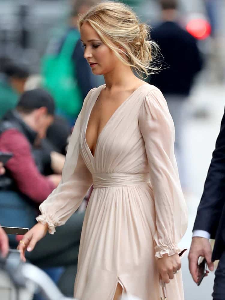 Jennifer Lawrence was seen walking the streets of Los Angeles on June 7, 2019. She wore a casual and carefree pink dress that went perfectly well with her blond messy low bun hairstyle with highlights and loose tendrils.