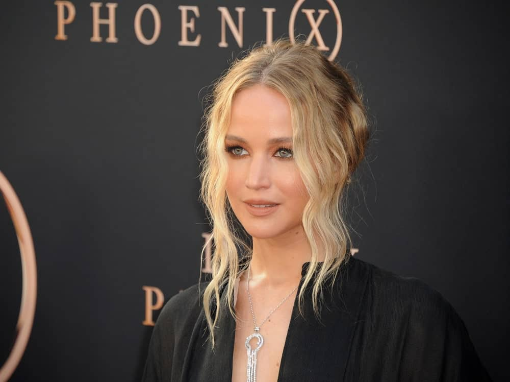 Jennifer Lawrence attended the Los Angeles premiere of 'Dark Phoenix' held at the TCL Chinese Theatre in Hollywood on June 4, 2019. She wore a simple black outfit that contrasted her highlighted messy bun hairstyle with loose and wavy curtain bangs.