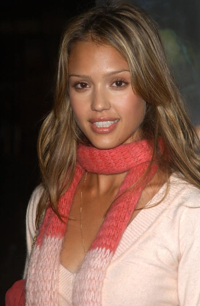 Actress Jessica Alba wore a simple yet lovely sweater with her scarf and medium-length highlighted layered brown hairstyle with long bangs at the world premiere of The Texas Chainsaw Massacre on October 15, 2003 in Hollywood.
