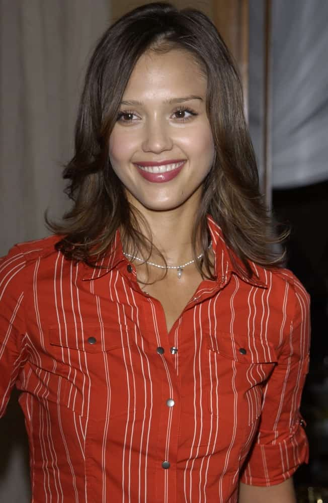 Actress Jessica Alba paired her red lips and red button down shirt with a dark shoulder-length hairstyle that has layers and long side bangs at the 4th Annual Self Day Celebration at the Peninsula Hotel in Beverly Hills on April 9, 2003.