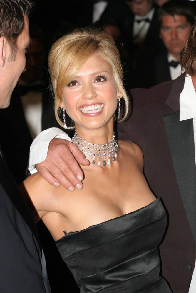 Actress Jessica Alba swept up her sandy blond hair into an upstyle that has loose tendrils and side-swept bangs when she attended the screening of 'Sin City' at the Grand Theatre during the 58th International Cannes Film Festival on May 18, 2005 in Cannes, France.