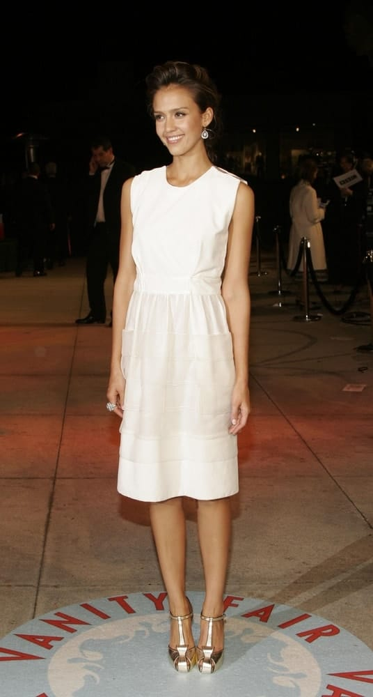 Jessica Alba wore a white and simple YSL dress at the Vanity Fair Oscar Party held at the Mortons Restaurant in West Hollywood, Los Angeles, CA on March 05, 2006. She paired this with a tousled upstyle bun hairstyle with highlights.