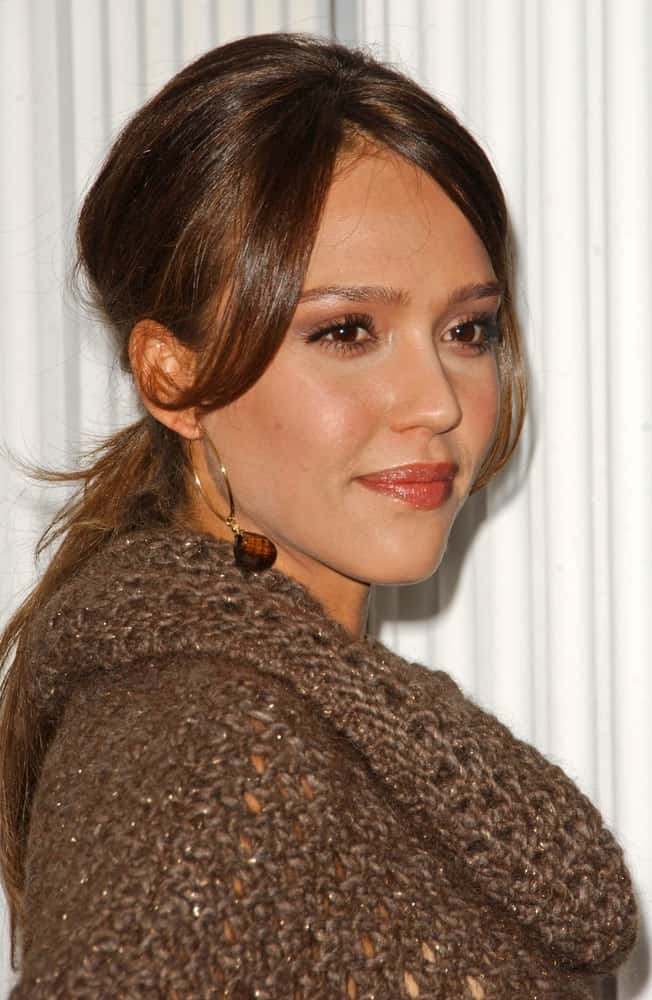 On April 19, 2007, Jessica Alba paired her simple gray knitted outfit with her simple low ponytail hairstyle with loose side bangs at the Escada 2007 Fall Winter Sneak Preview to Benefit Step Up Women's Network in Beverly Hills, CA.