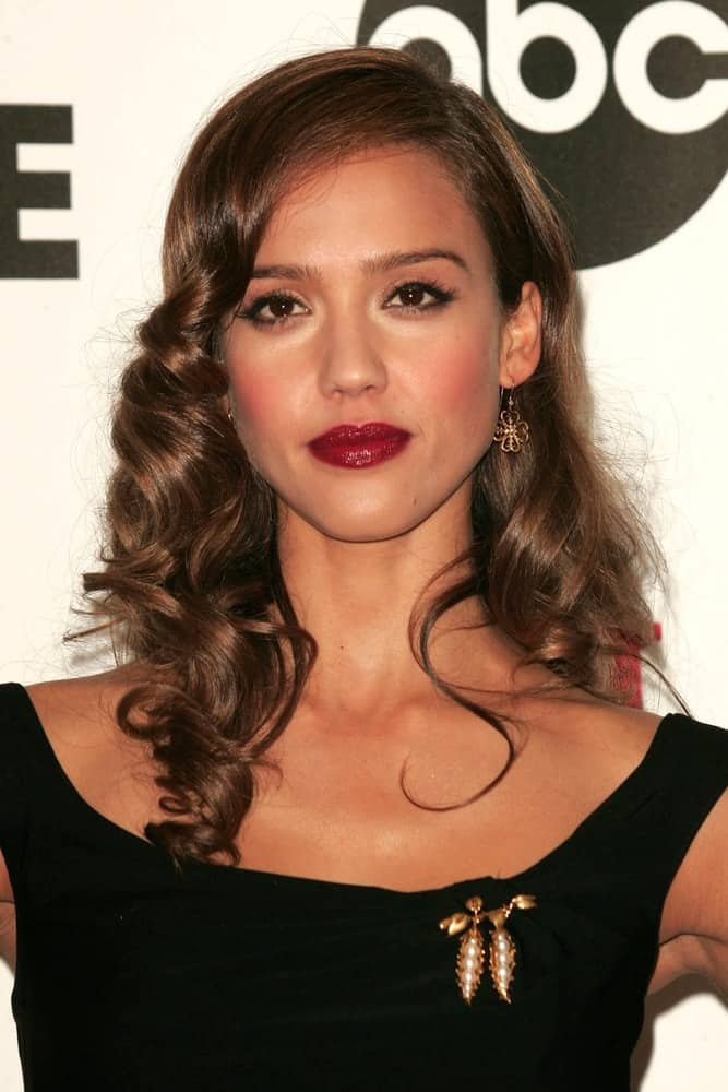 Jessica Alba was in the press room at the 2007 ALMA Awards in Pasadena Civic Auditorium, Pasadena, CA on June 1, 2007. She paired her charming black dress with bold red lips and a loose, tousled and curly side-swept hairstyle.