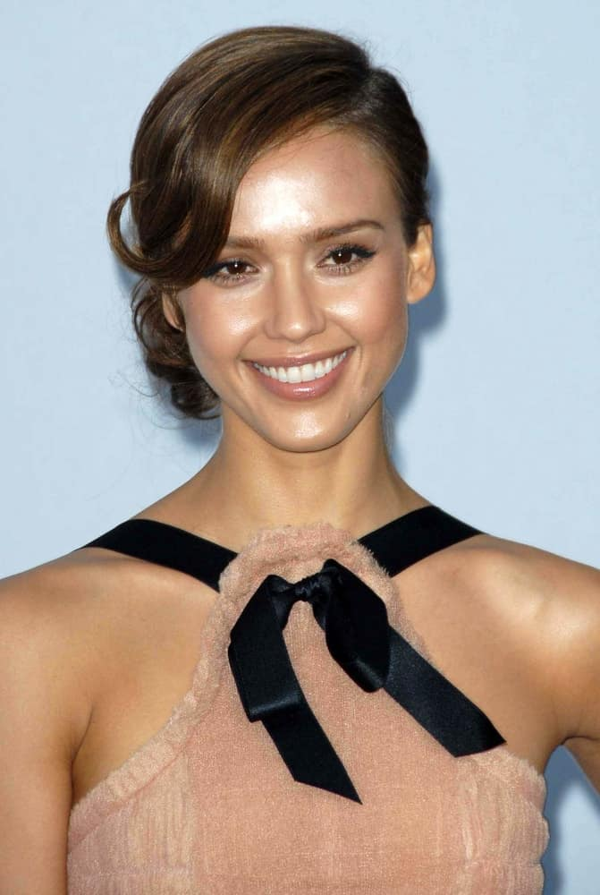 On May 18, 207, Jessica Alba wore a velvet beige dress with her low bun hairstyle that has loose side-swept bangs that has a flippy tip at the 2007/2008 Chanel Cruise Show Presented by Karl Lagerfeld in Hanger 8, Santa Monica, CA.