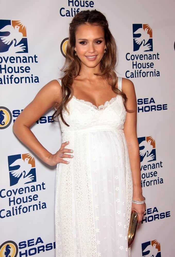 Jessica Alba wore a long white dress with her charming long and layered half-up hairstyle when she arrived at the Covenant House 2011 Gala on June 09, 2011 in Los Angeles, CA.
