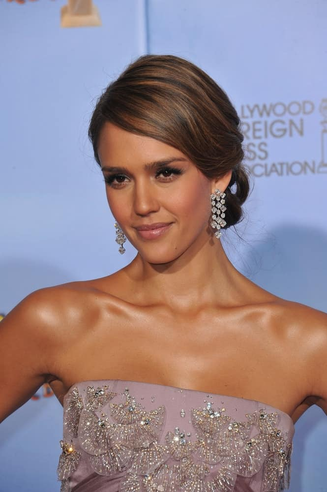 Jessica Alba paired her bejeweled strapless dress with her gorgeous diamond earrings and a messy low bun hairstyle with highlights and long side-swept bangs at the 69th Golden Globe Awards at the Beverly Hilton Hotel on January 15, 2012 in Beverly Hills, CA.
