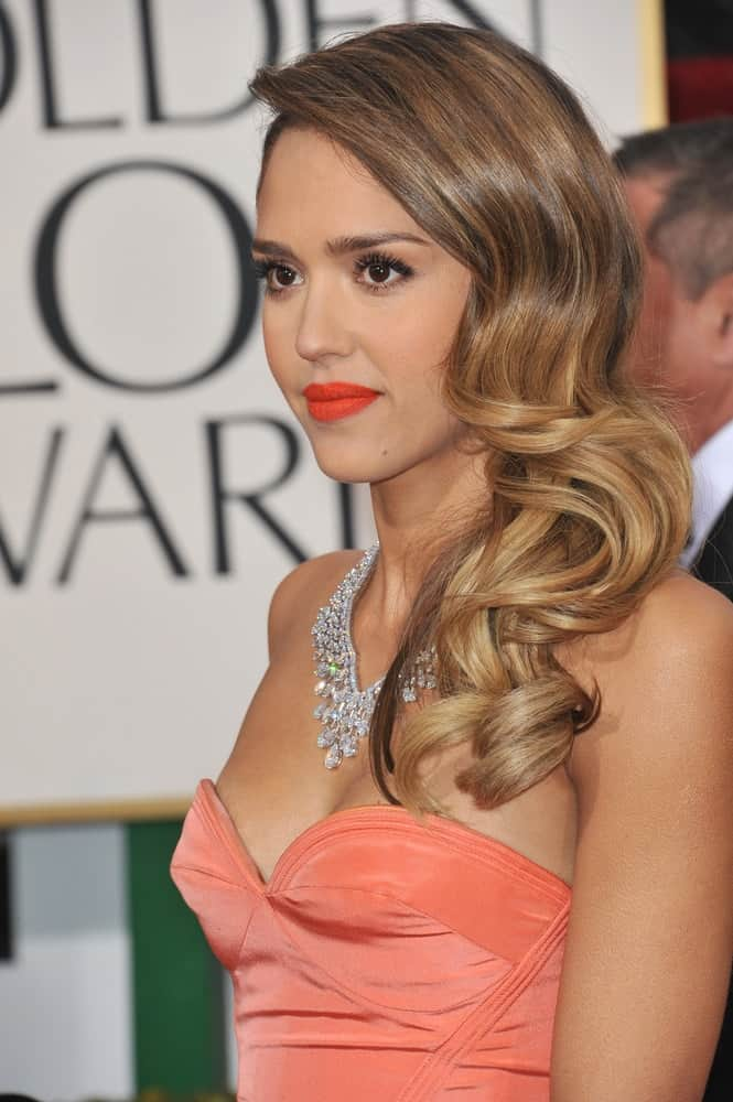 On January 13, 2013, Jessica Alba wore a charming and stylish orange dress that she perfectly paired with a long and side-swept curly hairstyle with highlights at the 70th Golden Globe Awards at the Beverly Hilton Hotel.