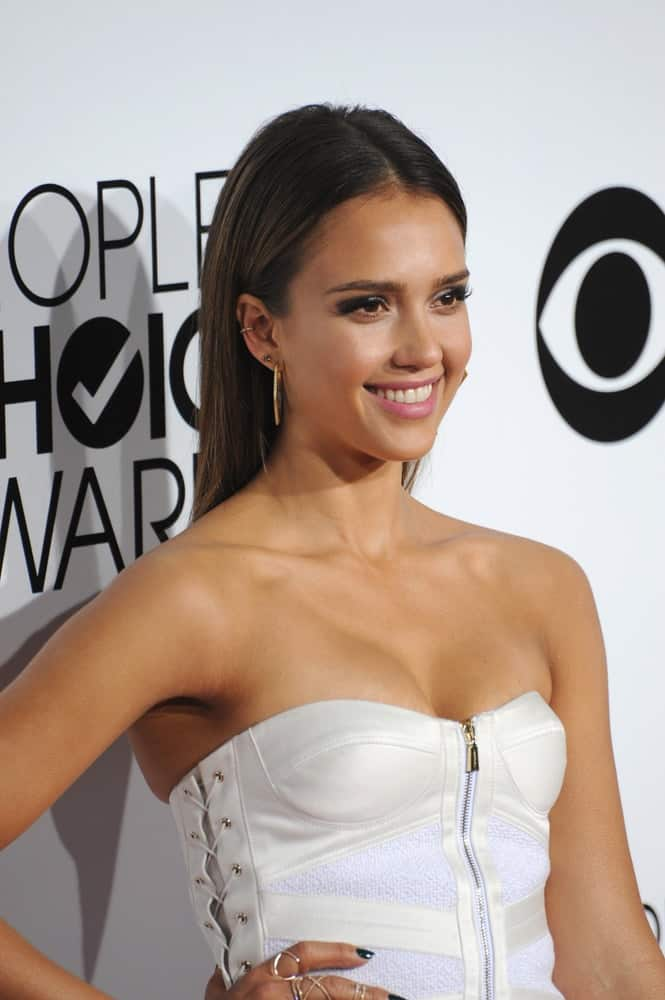 On January 8, 2014, Jessica Alba wore a bustier-type white dress with her long and slick straight brown hairstyle parted in the middle and tucked behind her ears at the 2014 People's Choice Awards at the Nokia Theatre, LA Live.