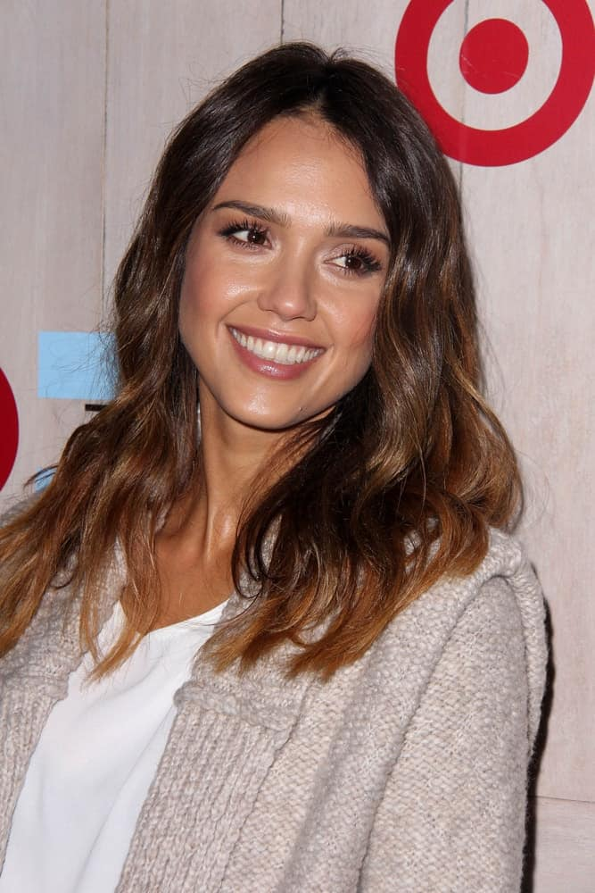 Jessica Alba wore a relaxed and casual sweater jacket with her loose and tousled medium-length hairstyle with highlights and layers at the TOMS for Target Holiday Partnership at the The Bookbindery on November 12, 2014 in Culver City, CA.