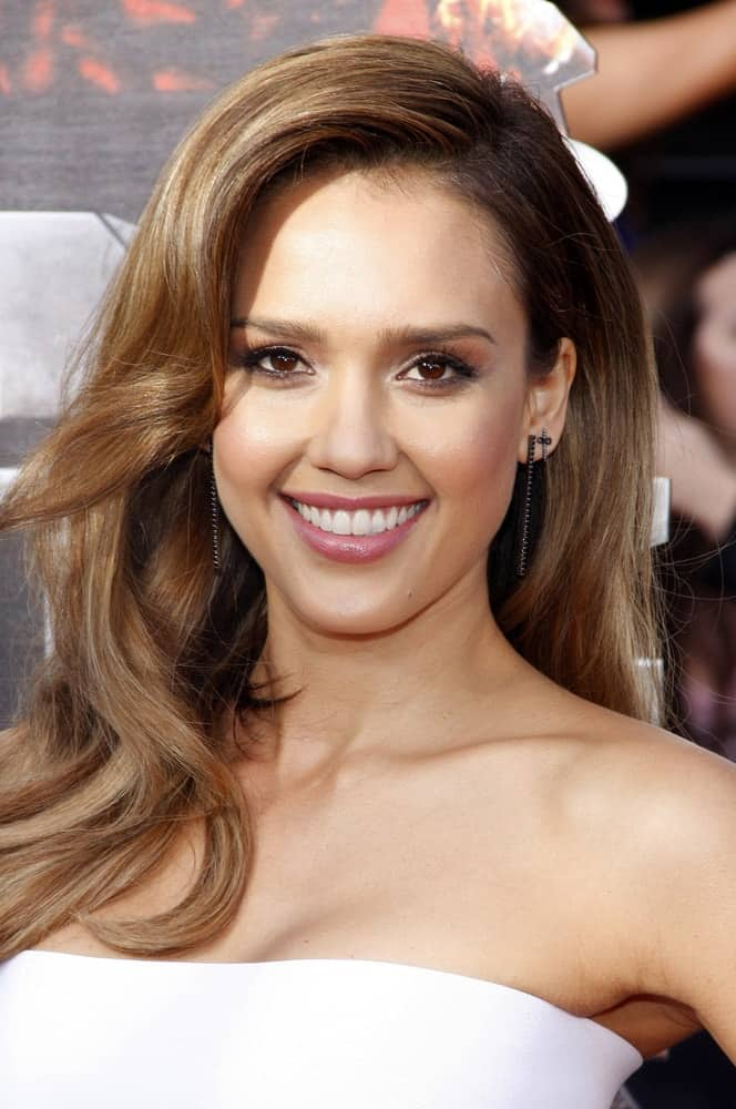 Jessica Alba was at the 2014 MTV Movie Awards held at the Nokia Theatre L.A. Live in Los Angeles on April 13, 2014 in Los Angeles, California. She was charming in her elegant white dress and long side-swept brown hairstyle with waves and layers.