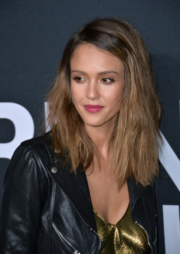On February 10, 2016, Actress Jessica Alba was at the Saint Laurent at the Palladium fashion show at the Hollywood Palladium. She wore a black leather jacket over her golden outfit and paired it with a clipped and tousled loose brown hairstyle with layers.