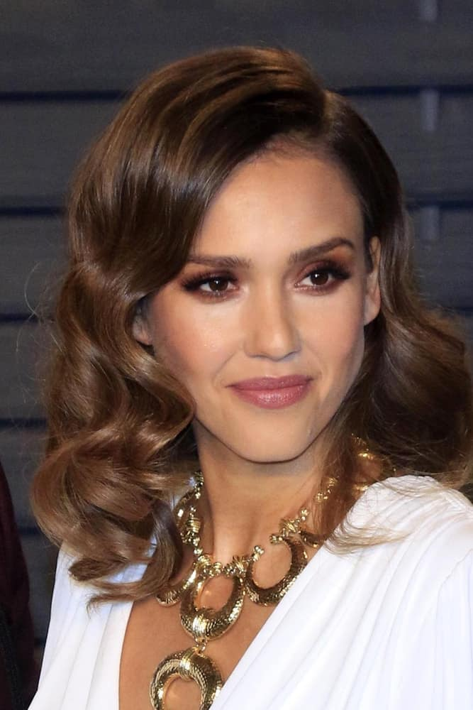 Jessica Alba was at the Bosch Season 2 Premiere Screening at the Silver Screen Theater at the Pacific Design Center on March 3, 2016 in West Hollywood, CA. She was charming in her white dress and matching medium-length side-swept curly brown hairstyle.
