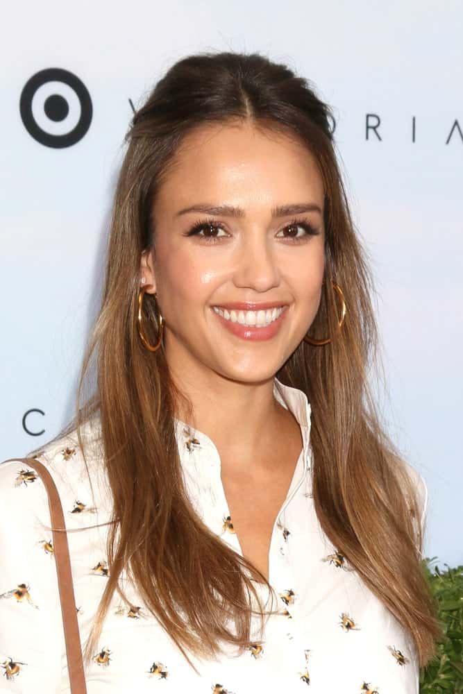 Jessica Alba attended the Victoria Beckham For Target Launch Event at a Private Residence on April 1, 2017 in Los Angeles, CA. She was seen wearing a lovely white patterned blouse to go with her straight brown hair in a half-up hairstyle.