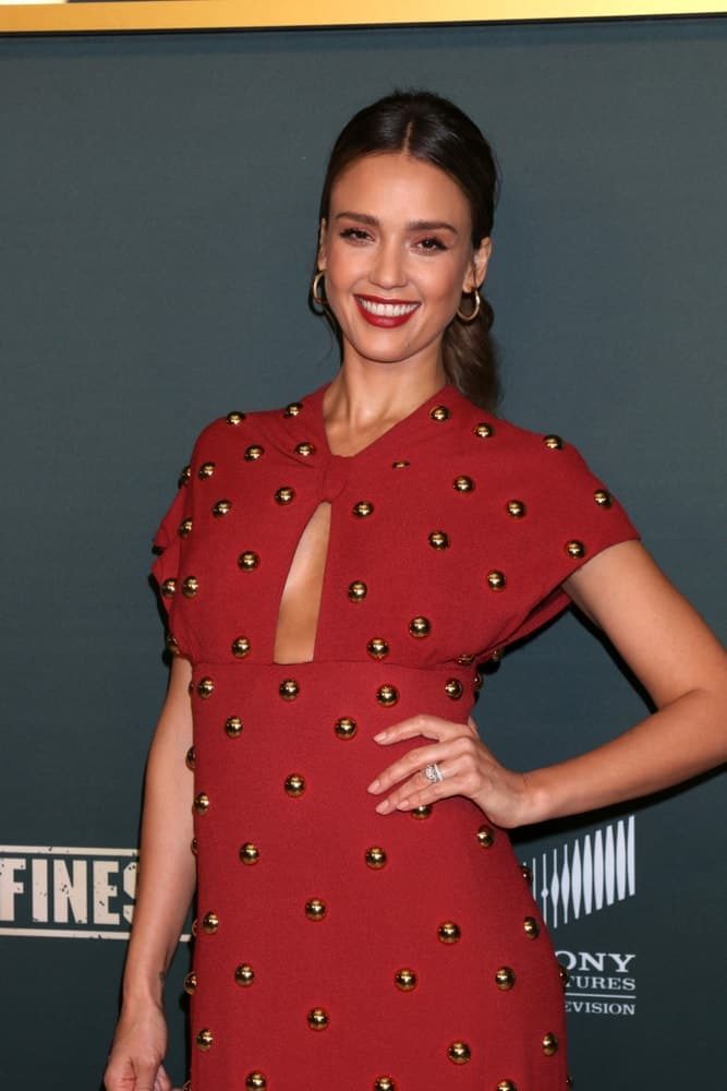 Jessica Alba wore a gorgeous red studded dress that matches well with her red lips and her long brown hair swept up for a ponytail at the