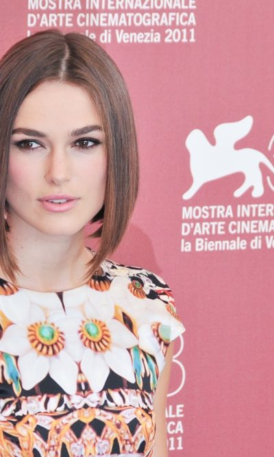 Keira Knightley poses at the photocall during the 68th Venice Film Festival at Palazzo del Cinema on September 2, 2011 in Venice, Italy. She wore a colorful floral dress with her straight bob hairstyle with a brown tone.