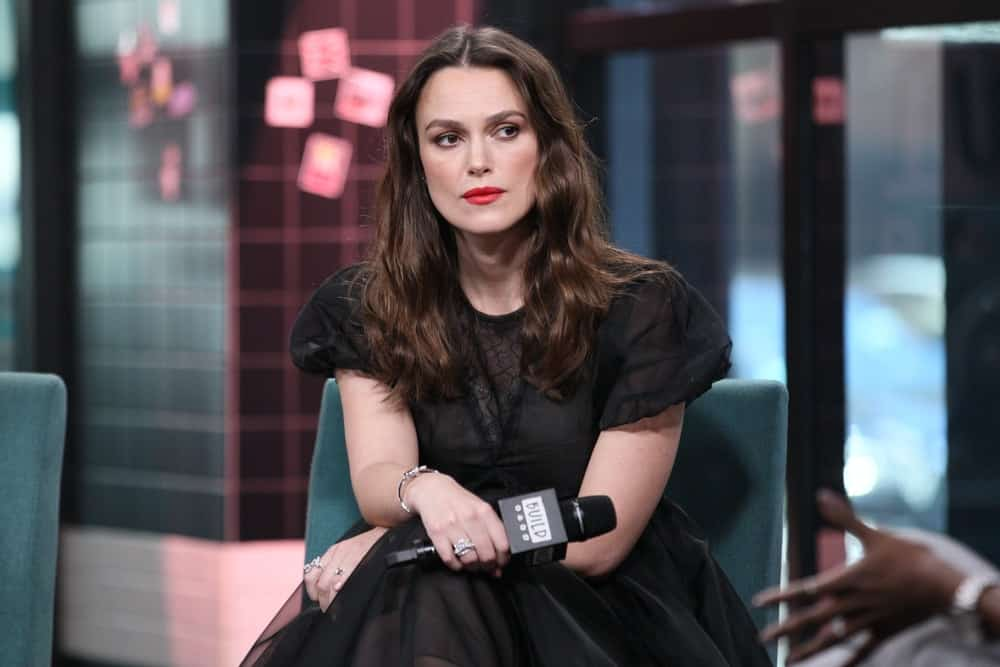 Keira Knightley was at The Tuesday show on March 12, 2019 at the BUILD Studio in New York, NY. She wore an elegant black dress to pair with her medium-length, loose and tousled wavy brunette hairstyle with subtle highlights.
