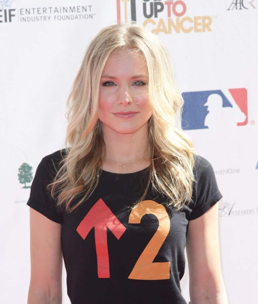 Kristen Bell in attendance for Stand Up To Cancer Fundraiser at Sony Pictures Studios, Los Angeles, CA on September 10, 2010. She had a blonde center-parted wavy hairstyle that contrasts her black shirt.