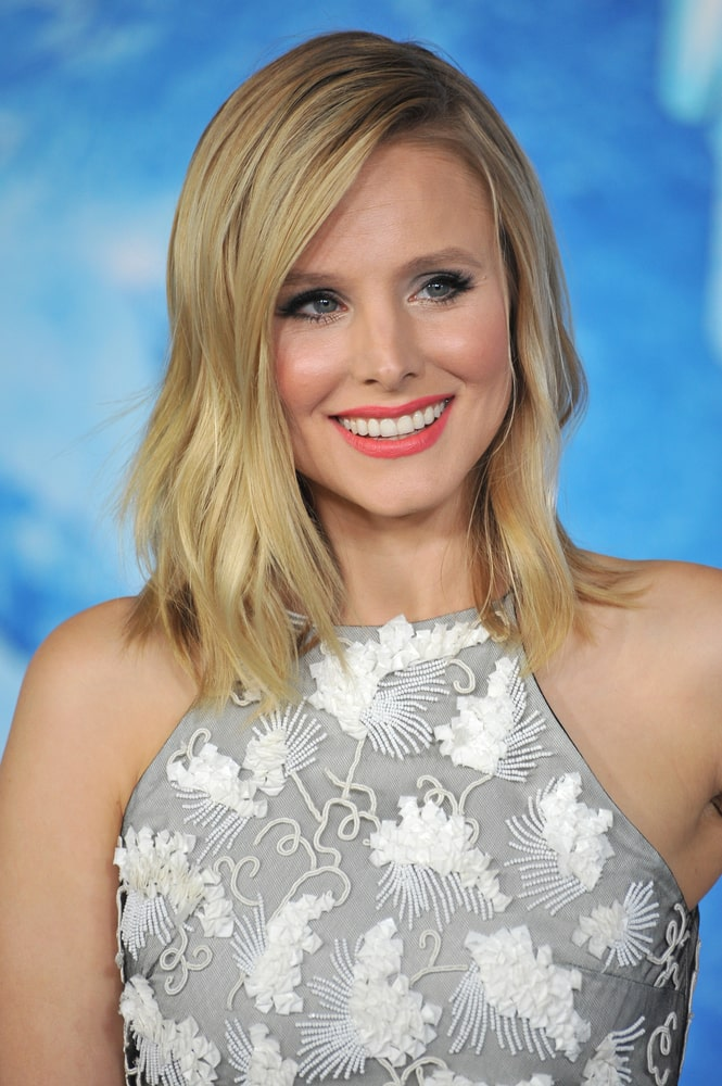 """Kristen Bell flashed a sweet smile while at the premiere of her movie """"Frozen"""" at the El Capitan Theatre, Hollywood on November 19, 2013. She opted for a loose wavy hairstyle that complements her gray halter dress."""