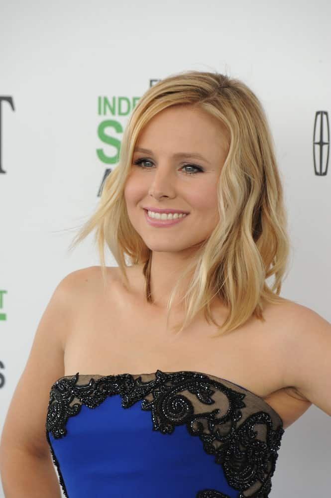 During the 2014 Film Independent Spirit Awards on March 1st, Kristen Bell sported a side-parted wavy hairstyle that goes perfectly with her blue tube dress and natural-looking makeup.