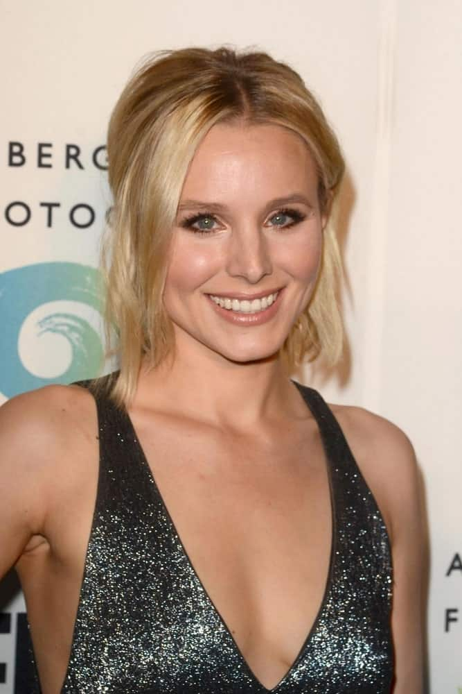 Kristen Bell shines in a sparkling black dress that complements her messy half updo during the Annenberg Space for Photography presents REFUGEE held on April 21, 2016.