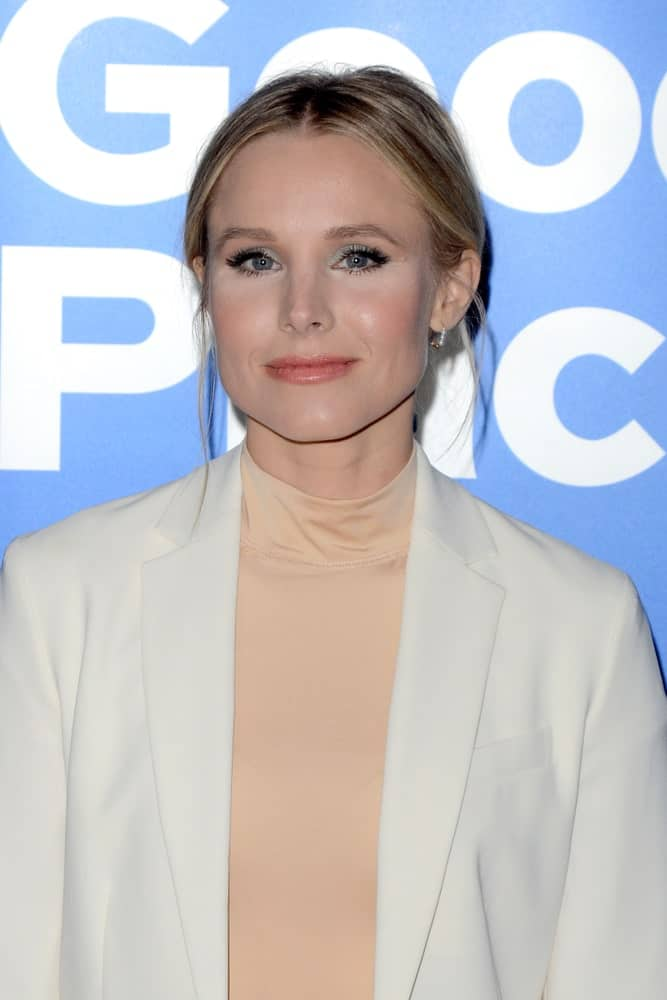 Kristen Bell with her highlighted blonde locks arranged into a messy center-parted upstyle with loose tendrils at