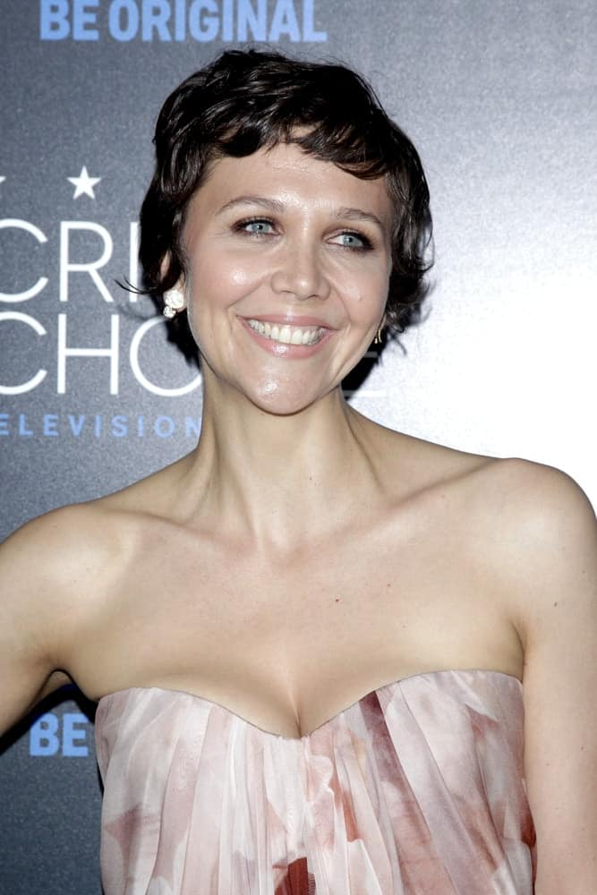 Maggie Gyllenhaal was at the 5th Annual Critics' Choice Television Awards at the Beverly Hilton Hotel on May 31, 2014 in Beverly Hills, CA. She paired her lovely beige strapless dress with a curly pixie hairstyle with side-swept short bangs.