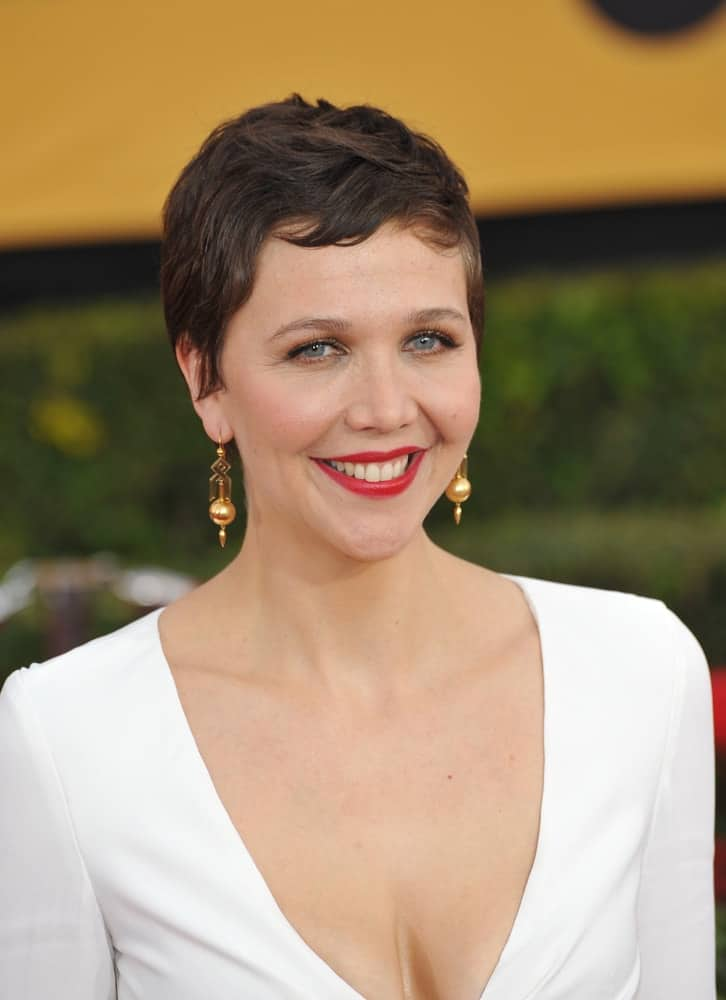 On January 25, 2015, Maggie Gyllenhaal was at the 2015 Screen Actors Guild Awards at the Shrine Auditorium. She paired her sexy white dress with a short pixie brunette hairstyle with short bangs.