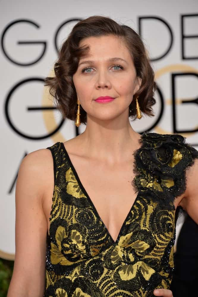 On January 10, 2016, Maggie Gyllenhaal attended the 73rd Annual Golden Globe Awards at the Beverly Hilton Hotel. She was stunning in a black and gold dress that she paired with her chin-length curly brunette hairstyle with layers.