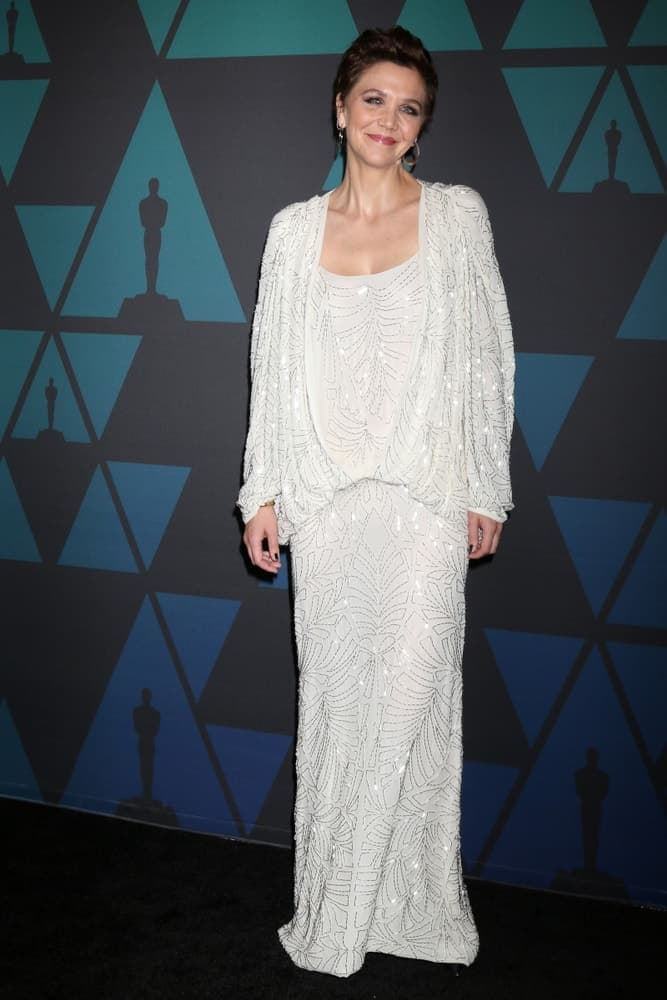 Maggie Gyllenhaal attended the 10th Annual Governors Awards at the Ray Dolby Ballroom on November 18, 2018 in Los Angeles, CA. She was stunning in a white dress to pair with her dark pixie brushed-back hairstyle.
