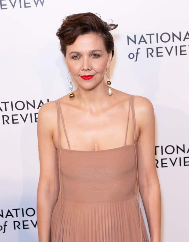 On January 8, 2019, Maggie Gyllenhaal wore a dress by A.W.A.K.E. when she attended the National Board of Review 2019 Gala at Cipriani 42nd Street. She paired her beige dress with a pixie tousled side-swept hairstyle.