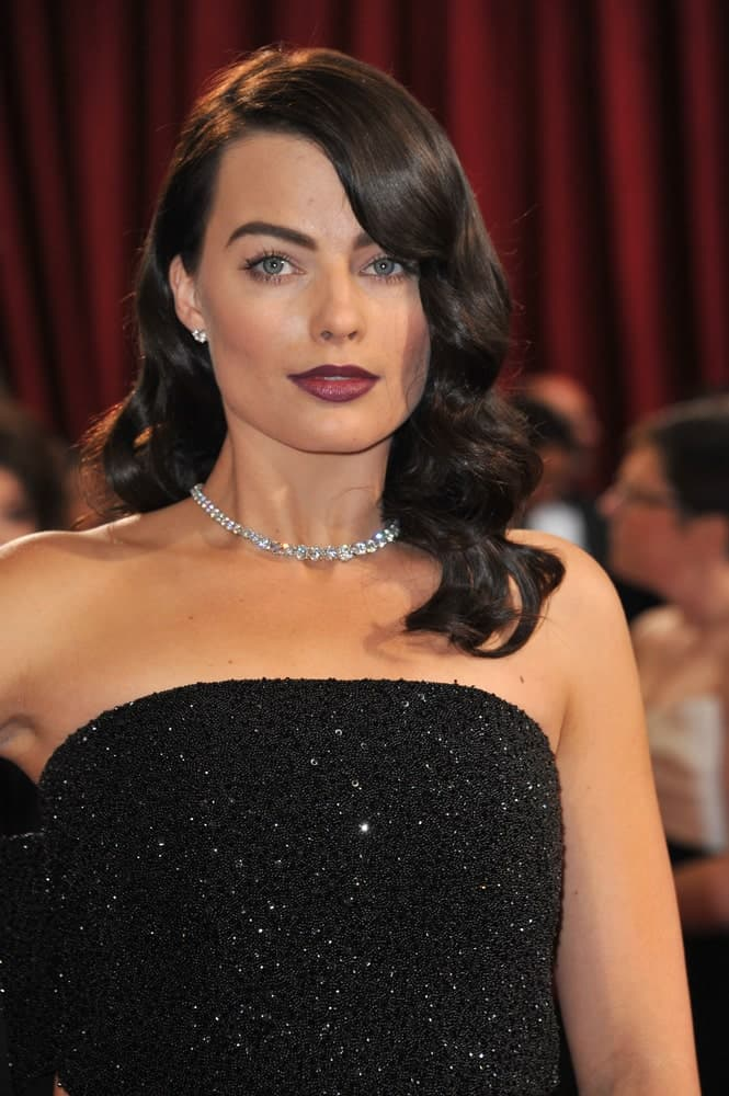 Margot Robbie exhibited a Hollywood glam look with her dark side-parted retro curls matching her sparkling black gown. This look was worn at the 86th Annual Academy Awards at the Dolby Theatre, Hollywood on March 2, 2014.