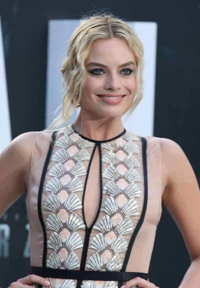 Margot Robbie with her blonde wavy upstyle hair at the European premiere of The Legend Of Tarzan on July 5, 2016. She is wearing a sheer long dress that's very classy and elegant.
